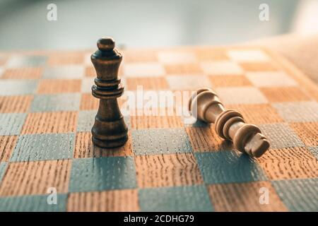 Concetto vincente del gioco degli scacchi. La vittoria si muove con l'ultimo pezzo in piedi su tavola di legno di scacchiera