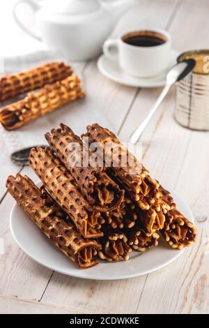 Composizione di natura morta, tubuli di cialde con crema e marmellata di latte, tazza di caffè su sfondo bianco di legno, cibo e concetto di cottura casalinga in rustica sty Foto Stock