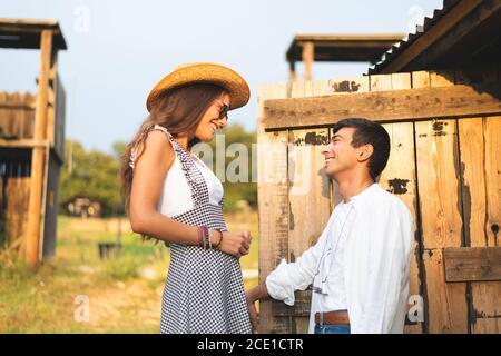 Una coppia che si guarda e si sorride alla porta anteriore di un carro di legno. Ranch Concept Photography Foto Stock