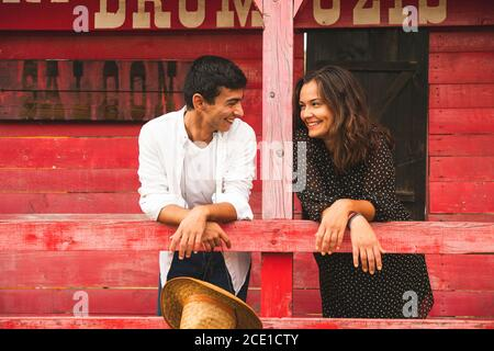 Bella coppia Flirtare e sorridere fuori di un Red Wooden Saloon. Ranch Concept Photography Foto Stock