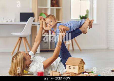 La mamma intrattiene il piccolo figlio sollevandolo sui piedi in una luminosa stanza dei bambini. Foto Stock