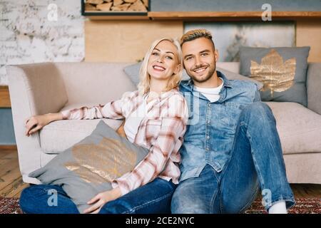 Giovane felice coppia ritratto rilassarsi e abbracciare a casa Foto Stock