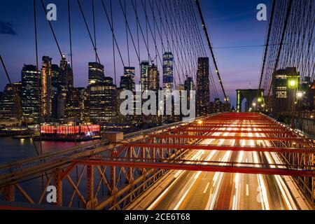 Grattacieli di Lower Manhattan al Dusk e al Ponte di Brooklyn con sentieri luminosi. Serata a New York City, NY, USA