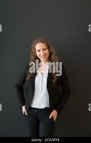 Bella giovane donna bionda in abito elegante scuro in piedi con sicurezza con le braccia incrociate e guardando la fotocamera sorridente su nero sfondo