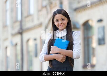 Leggi per conoscere e sapere come. Happy kid tenere libro all'aperto. Biblioteca scolastica. Istruzione informale. Lezione di lettura. Imparare a leggere. Lettura a casa. Letteratura e lingua. Senti il bisogno di leggere. Foto Stock