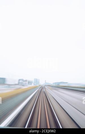 Scatto non focalizzato del treno veloce in movimento sulla ferrovia con il paesaggio urbano intorno, Danimarca Foto Stock