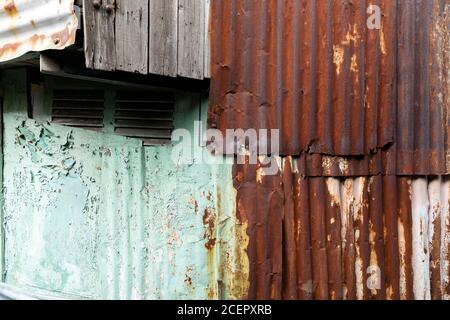 tessuti di ferro corrugato, legno, peeling vernice su una vecchia casa in un quartiere povero Foto Stock