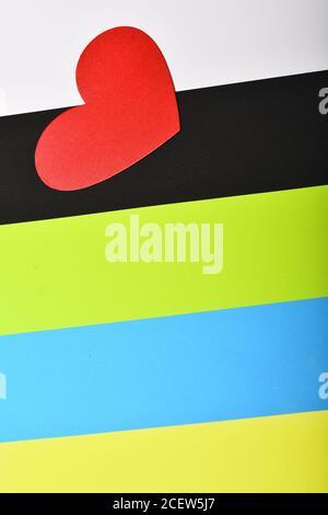 Simbolo di amore e strisce colorate. Cuore di carta rosso su sfondo colorato, vista dall'alto. Concetto di amore e vacanza. Carta giornaliera di San Valentino. Foto Stock