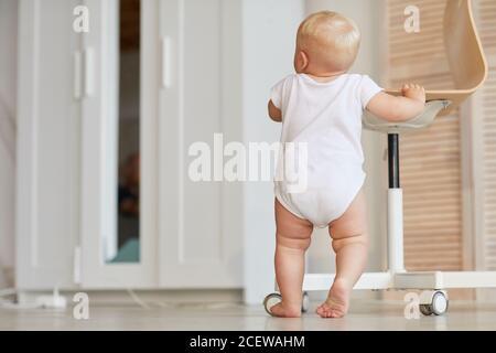Vista posteriore di un bambino irriconoscibile che tiene sulla sedia imparando a stare in piedi e camminare sulle gambe, copia spazio