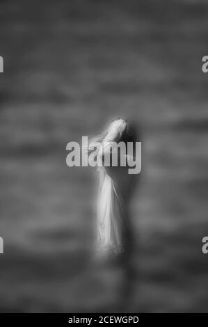 Immagine surreale in bianco e nero sfocato di donna irriconoscibile in piedi in acqua.