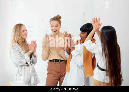 Donne sorpresate in abbigliamento casual in ufficio insieme, in shock con bocca aperta. Celebrare la loro vittoria in progetto di affari, buon lavoro di diverse donne Foto Stock