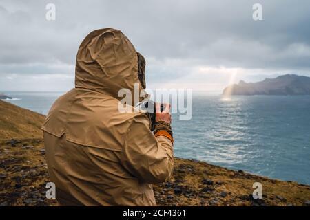 Vista posteriore di un uomo anonimo in abiti invernali con un Fotocamera all'aperto nel paesaggio delle Isole Faroe Foto Stock