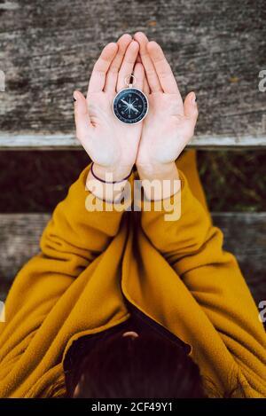 Da sopra anonima femmina che tiene in mano una piccola bussola vintage su tavolo di legno durante il viaggio in campagna Foto Stock
