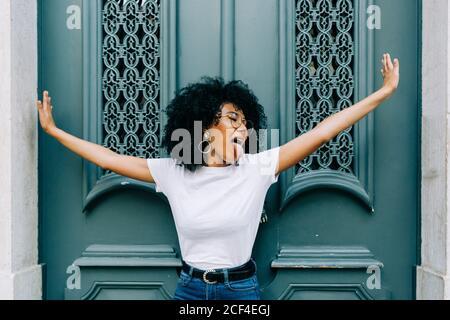 Giovane afroamericana in piedi con occhi chiusi di verde porta in legno e linguetta di uscire di giorno Foto Stock