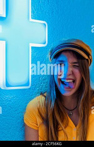 Felice giovane donna in camicia gialla e berretto alla moda fare divertente grimace e mostrare la lingua contro la parete blu con segno al neon della croce medica