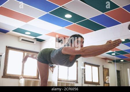 Concentrato sottile femmina in piedi in guerriero 3 posa durante il fare yoga in uno spazioso monolocale