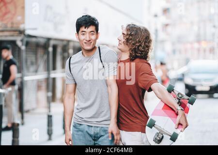 Spensierati interessati uomini multietnici in abiti casual con longboard gesturing e parlando mentre passeggi lungo la strada della città