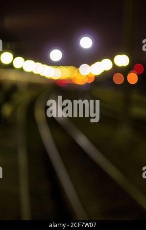 Sfondo sfocato con sagome di binari ferroviari e illuminazione notturna dell'orientamento verticale della stazione ferroviaria