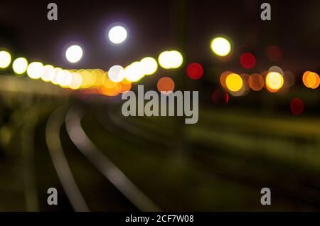 Sfondo sfocato con sagome di binari ferroviari e illuminazione notturna della stazione ferroviaria