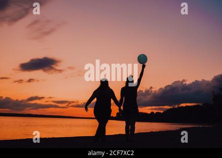 Vista posteriore di donne anonime con palloncino che tiene le mani e. camminando lungo la riva del mare durante il bellissimo tramonto Foto Stock
