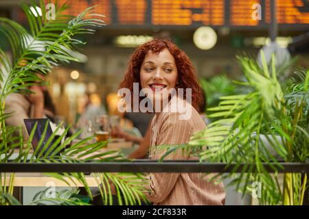 Allegro giovane donna lavora sul computer portatile in cafe