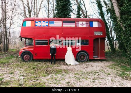Sposa in elegante abito da sposa e sposo in abito di classe in piedi vicino al bus rosso vintage durante il giorno del matrimonio e cercando alla telecamera Foto Stock