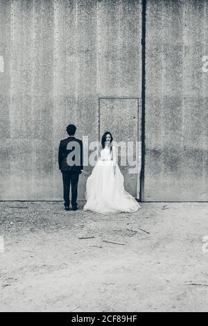 Groom bianco e nero in elegante smoking e sposa abito da sposa bianco in piedi sullo sfondo di un edificio shabby durante giorno di nozze Foto Stock