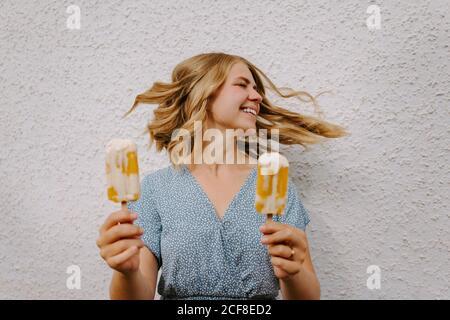 Femmina con gli occhi chiusi facendo simpatici grimace volti con gustoso lecci di ghiaccio su bastoni su sfondo bianco