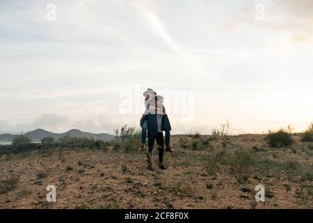 Uomo a corpo pieno che dà cavalcata piggyback alla ragazza felice mentre in piedi in campo contro il cielo nuvoloso tramonto in natura Foto Stock