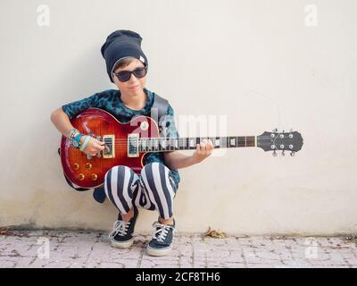 Ragazzo vivace eccitato in abiti colorati che suonano la chitarra seduto appoggiandosi sullo sfondo di una parete bianca Foto Stock