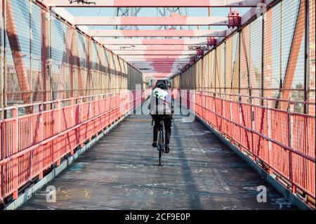 Vista posteriore di ciclista anonima con casco bici da corsa tra Struttura a ponte in metallo rosso nella città di New York Foto Stock