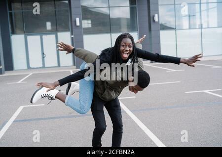 Uomo etnico che dà cavalcata piggyback alla ragazza afro-americana eccitata con braccia allungate mentre si diverte nel parcheggio esterno edificio moderno Foto Stock