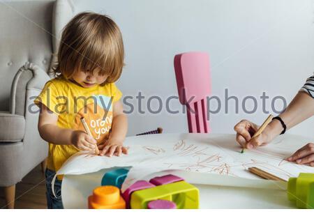 Mano adulta tagliata irriconoscibile aiutando carina bambina in giallo camicia seduta al tavolo con matite colorate durante la spesa tempo in sala giochi in asilo Foto Stock
