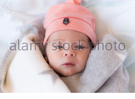 Dall'alto di adorabile bambino neonato avvolto in coperta con cappello rosa sulla testa guardando la fotocamera mentre si sdraia su letto bianco Foto Stock