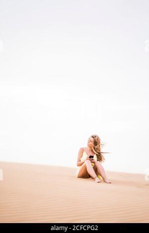 Donna bionda elegante e premurosa che utilizza il telefono cellulare mentre si è seduti Il mezzo del deserto del Marocco