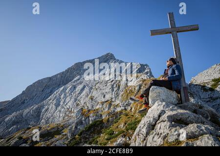 L'uomo gode di sole mentre si siede di fronte alla croce sommitale a Osterfelderkopf, sullo sfondo l'Alpspitze, rock, cielo blu, Garmisch-Partenkirchen,