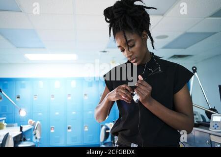 Donna afro-americana specializzata con dreadlock che si regola e si accende lampada di occhiali binoculari mentre si lavora in laboratorio contemporaneo