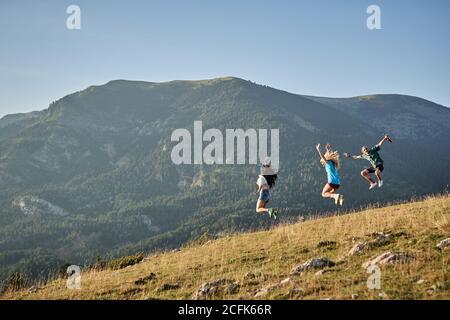 Compagnia di amici felici che saltano in collina in montagna mentre libertà durante le vacanze estive Foto Stock