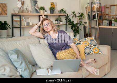 Mature bionda rilassato uomo d'affari in casualwear seduto sul divano a. casa Foto Stock