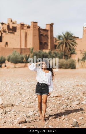 Giovane donna riccia orientale aspetto camminare sullo sfondo di kasbah Ait-ben-Haddou. Viaggio in Marocco, Ouarzazate. Vacanze estive, concetto di stile di vita di viaggio.