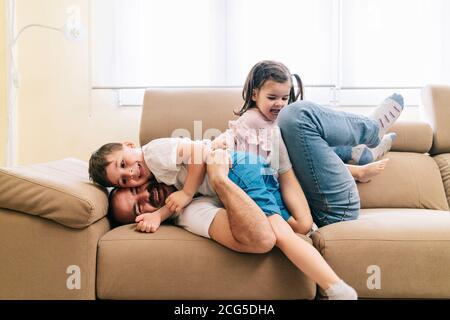 Un padre gioca con i suoi figli sul divano