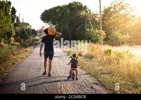 Bambina piccola, in bicicletta, con il suo giovane padre che porta una grande zucca halloween su una strada di campagna al tramonto. Vista posteriore. Foto Stock