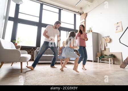 felice famiglia madre padre e figlia che ballano a casa Foto Stock