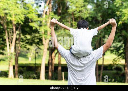 Papà che dà il figlio giro sul retro nel parco. Famiglia asiatica carino e caldo. Padre e bambino che si divertono all'aperto. Foto Stock