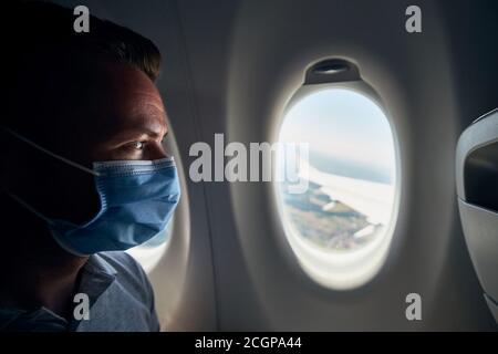Uomo che indossa la maschera all'interno dell'aereo durante il volo. Temi nuovo normale, coronavirus e protezione personale.