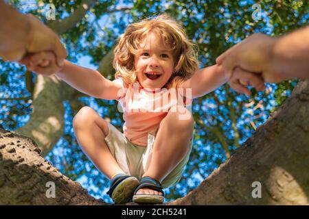 Padre che aiuta il figlio a salire un albero. Ragazzo felice che arrampica un albero durante il periodo estivo. Mano dei padri. Protezione dei bambini. Foto Stock