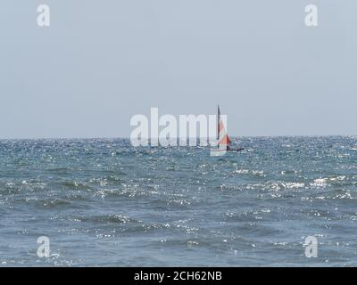 piccola barca a vela sovrastata dalle onde nel ruvido mare in una soleggiata giornata estiva