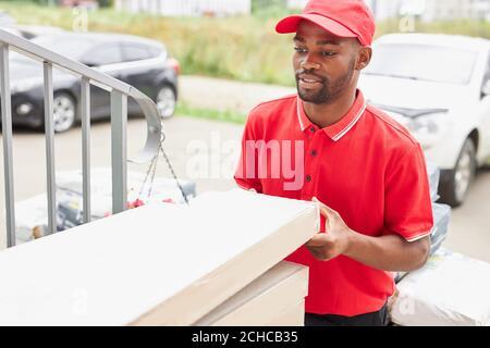 il giovane uomo nero africano lavora in azienda di consegna, è venuto ai clienti per dargli, indossando uniforme rossa