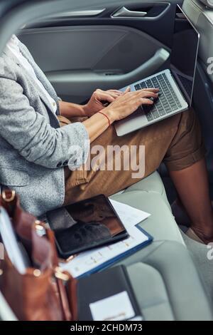 Lavorando online in taxi, foto verticale di donna d'affari utilizzando il computer portatile mentre si siede sul sedile posteriore in auto