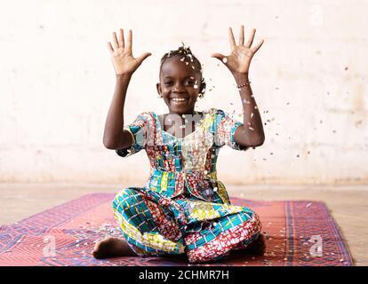 African Fun Party Girl, donna sorridente che lancia i confetti, contro uno sfondo bianco con Copy Space